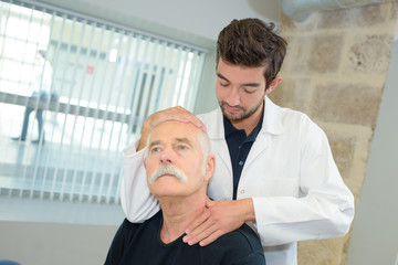 young physiotherapist massaging the neck of senior patient