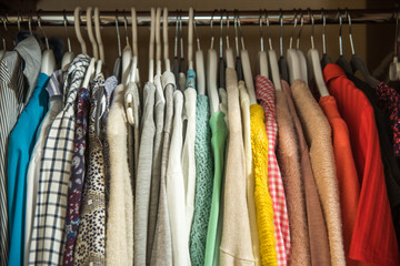 Different clothes on hangers . Multi-colored dresses and sweaters.