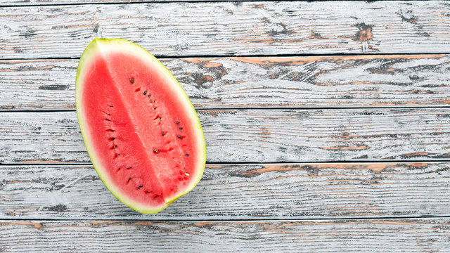 Fresh ripe watermelon. Melon. On a white wooden background. Free space for text. Top view.