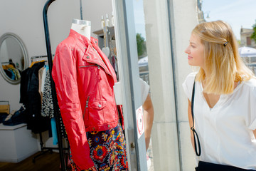 Lady looking at outfit on mannequin in shop window