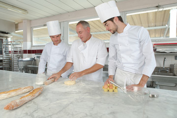 male chefs and assistant working at kitchen