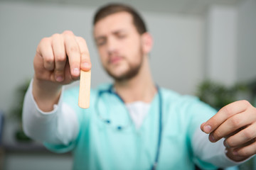 male doctor holding stick to look in patients throat