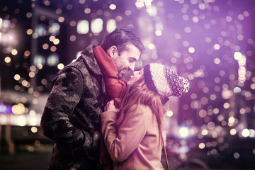 pretty young loving couple is kissing romantically at night
