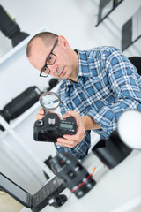 portrait of a focused man fixing camera at his workplace