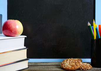 Back to school, education concept. Books, useful  whole-grain cookies and apple on classroom table in front of blackboard. Copy space. You will be healthy and smart with apple, whole-grain cookies