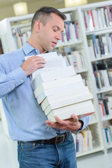 Man carrying a precarious stack of books