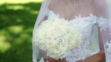 1642e0bb809 0 05 Young beautiful bride in wedding white dress with bridal bouquet of  white roses staying in a