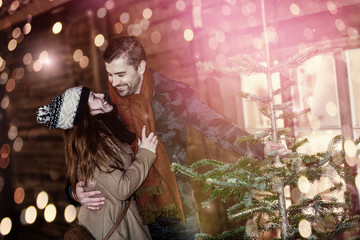 pretty young loving couple are buying a Christmas tree at the Christmas market