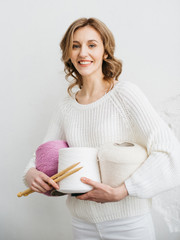 Happy young woman with wool yarn and knitting needles