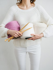 Woman with wool yarn and knitting needles