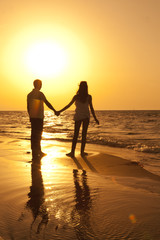 Romantic pair holding hands in the hot sunset