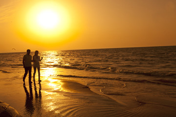 Romantic couple walking in the seaside in the sunset