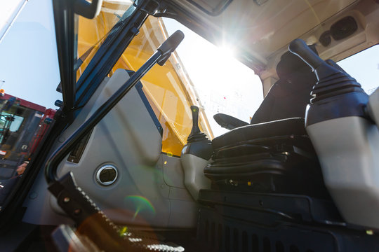 Modern ergonomic and stylish dashboard of heavy semi truck with lots of equipment, Steering column, indicators, buttons, and other electronics, integrated into interior of large commercial truck cab.