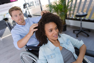 disabled hairdresser with client at salon