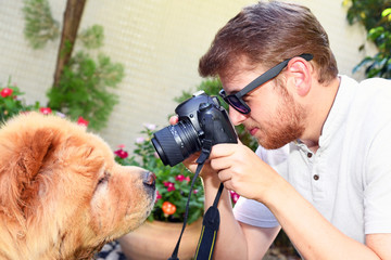 A handsome white young man with sunglasses and a beard taking a picture of his Chow Chow dog a sunny day in a park