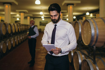 Winemakers in wine cellar holding glass of red wine and checking it. Sommeliers testing wines in winery.