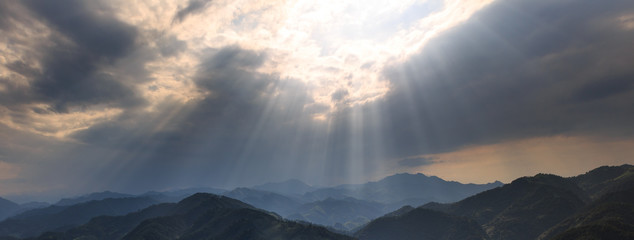 Rays of Sunshine Abstract Graphic Resource. Panoramic Mountains, Clouds and Bright Rays of Light Shining through an opening in the clouds. Sign from heaven concept, brilliant light from above. Fotoväggar