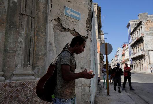 A man eats a hotdog as he carries his guitar on the streets of Havana