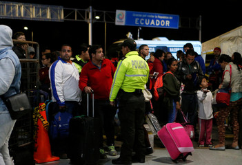 Venezuelan migrants stand in line to register their entry into Ecuador at the Rumichaca International Bridge
