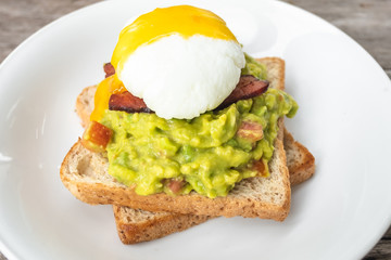 bread, avocado sauce, bacon, spinach, egg benedict on the white plate and old wood background, avocado sauce combine avocado and tomatoes, breakfast
