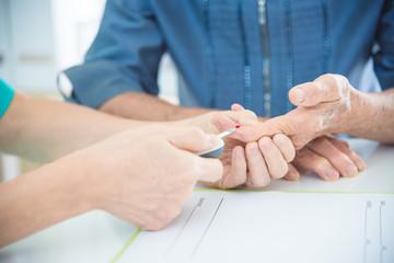 Nurse's hands Using Glucometer On Senior female Patient's Finger