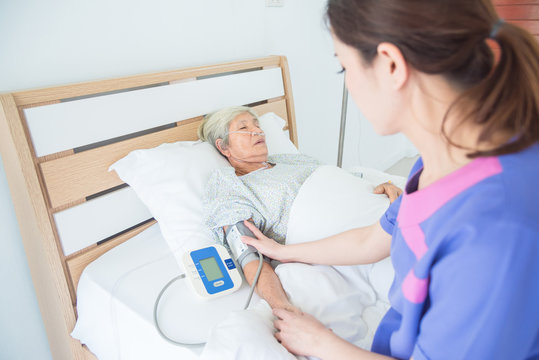 Nurse checking blood pressure of senior female patient who sleeping on bed
