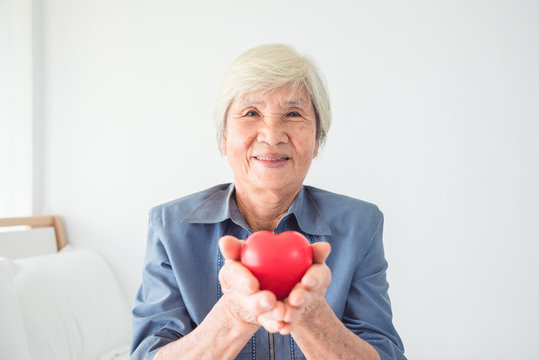 Senior female with white color hair holding heart shape ball and smiling at camera