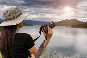 Female photographer taking pictures of a sunset. Travel and hobbies.