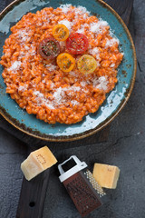 Turquoise plate with tomato risotto, view from above, vertical shot, close-up
