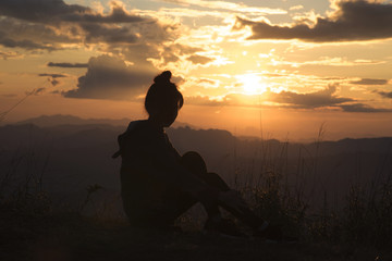 Silhouette of the Young woman looking at sunset on top mountain
