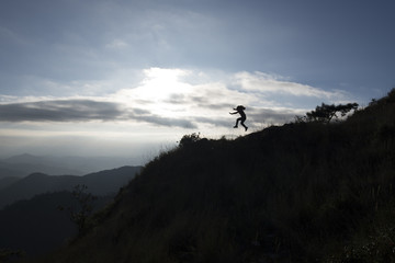 Silhouette of a woman jumping on top mountain
