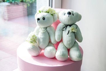 two toys - white bears, sitting on a pink box at the window, wedding
