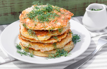 Delicious pancakes from courgettes and fresh vegetables with sour cream and dill
