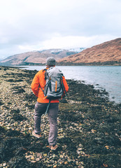 Trekking in mountain, highlands scotish landscape, traveler with backpack walks on lake shore