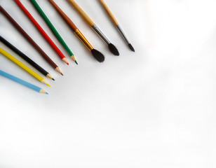 Pencils and brushes lie on a white background on the table