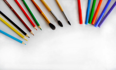 Bright pencils, brushes and markers are on the table