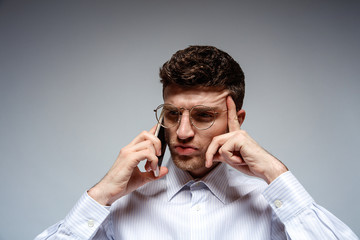Handsome young man in eyeglasses and white shirt is thinking while talking on the mobile phone, on grey background