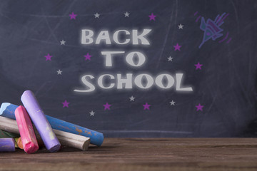 message back to school on blackboard background with rockets and stars