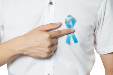 Men's healthcare concept - close up of male hand pointing to light blue ribbon for prostate cancer at left chest isolated on white background.