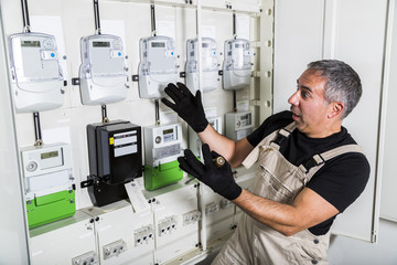 Funny electrician doing electrical repair in switchboard