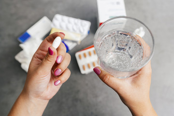 one round white pill in young female hand and Glass of Water for medication. Health care and medical concept.
