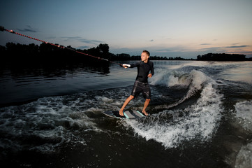 Wakesurfer riding down blue river waves with splashes