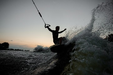 Active man riding on a wake board at the evening
