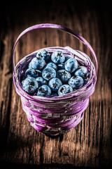 Bilberries in basket on vintage wooden board