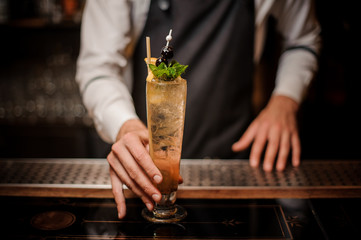 Bartender holding a glass with fresh and sweet summer cocktail