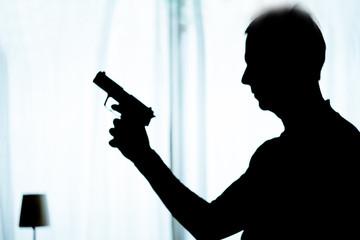 Silhouette of man wielding a gun