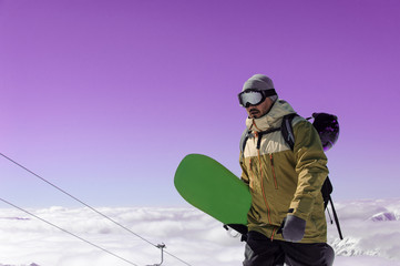man with a green snowboard in his hand walking along the snow to a mountain lift
