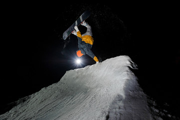 snowboarder riding down the snowy mountain slope at the dark night