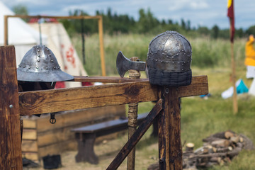 Metal helmets and an ax on the blurred background of a medieval military camp. Reconstruction of battles.