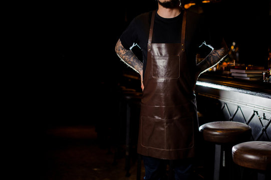 Barman with tattoo dressed in dark brown leather apron near bar counter